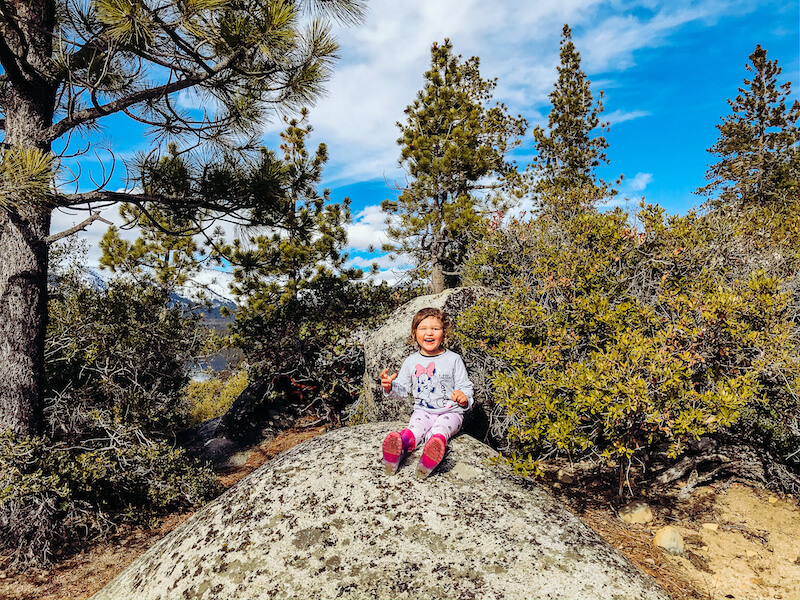 A little girl sitting on a rock surrounded by trees and smiling.