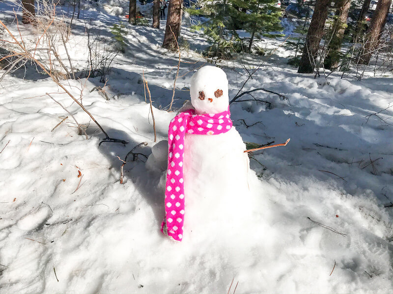 A snowman with a pink polkadot scarf around its neck.
