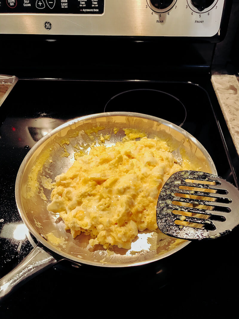 A pan full of scrambled eggs on an electric stove top.