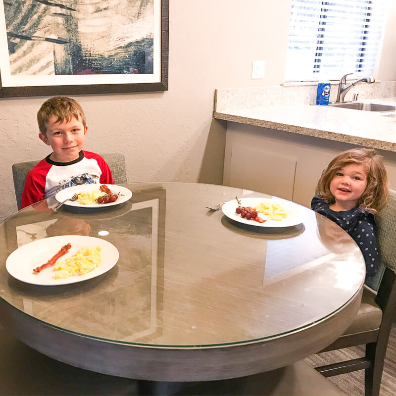 Two kids sitting at a table with plates of bacon and eggs in front of them.