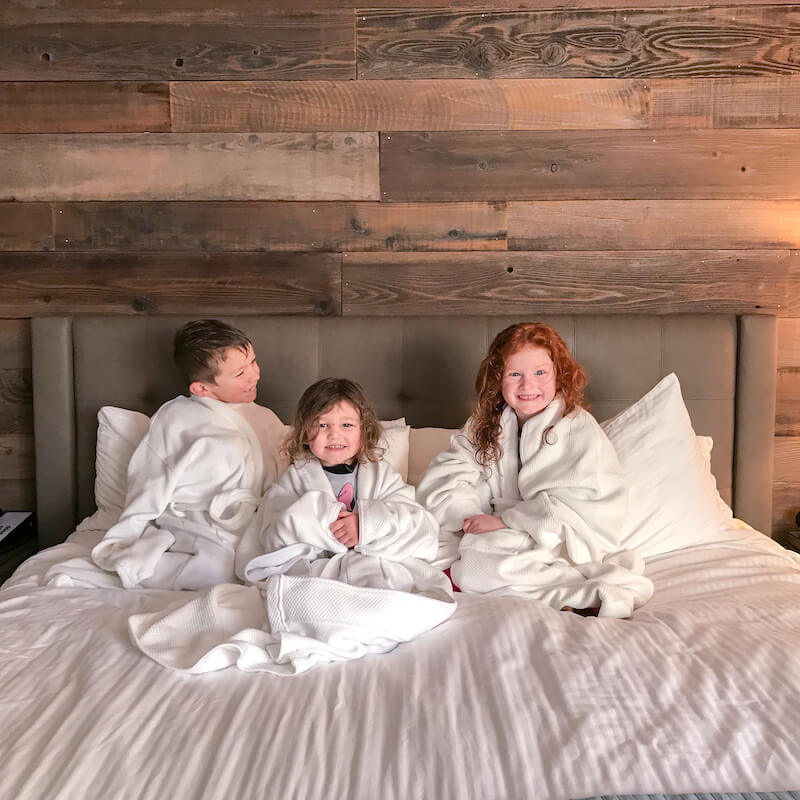 Three kids in white hotel robes sitting on a king sized bed with white bedding.
