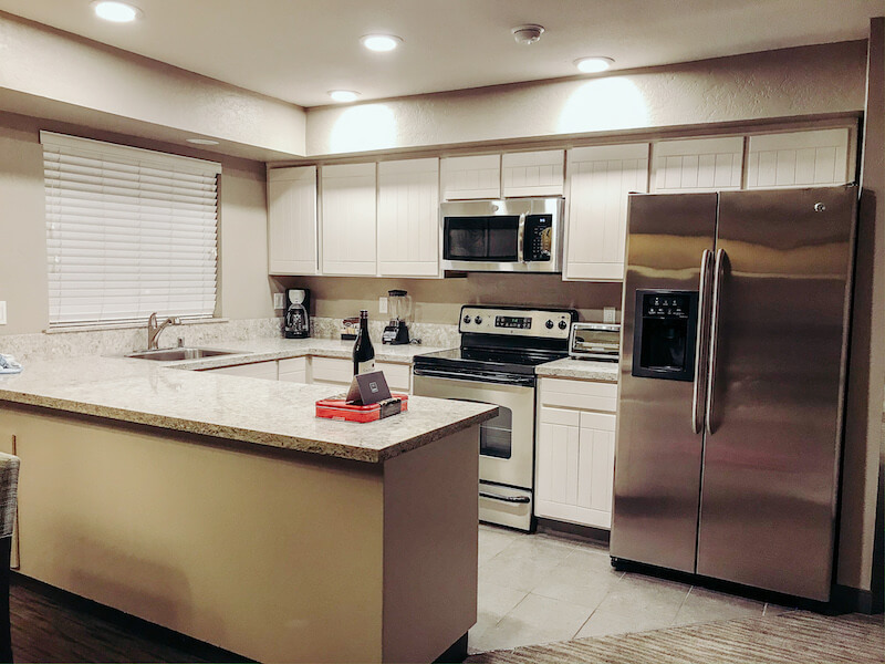 A full sized modern kitchen with stainless steel appliances.