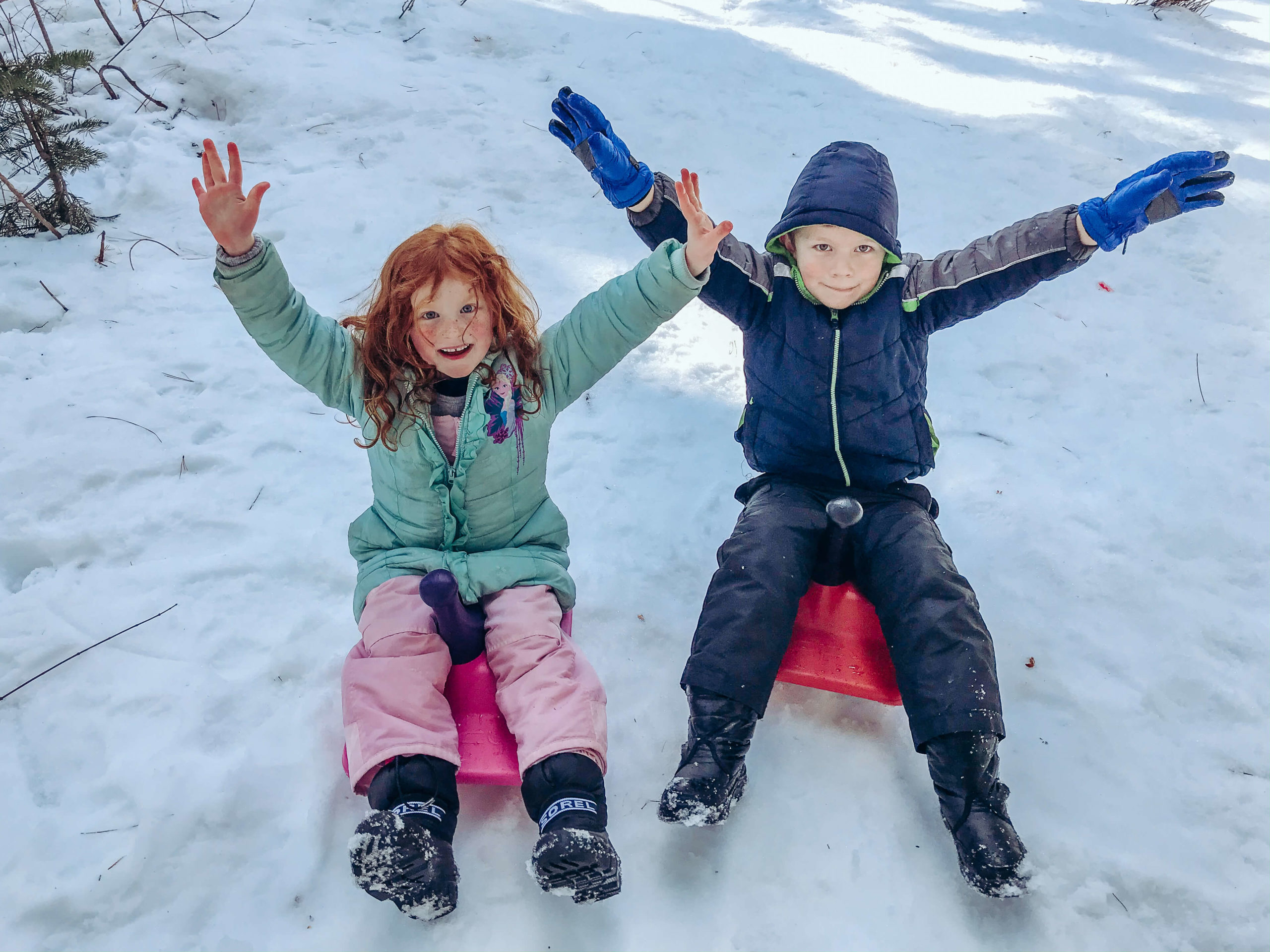 Two kids sitting on sleds with their arms up, surrounded by snow.