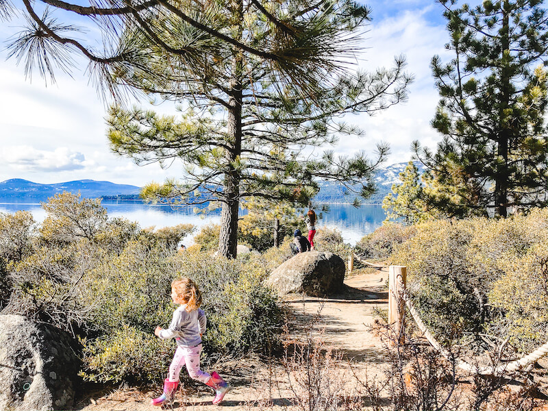 A little girl running along the trail next to Lake Tahoe.