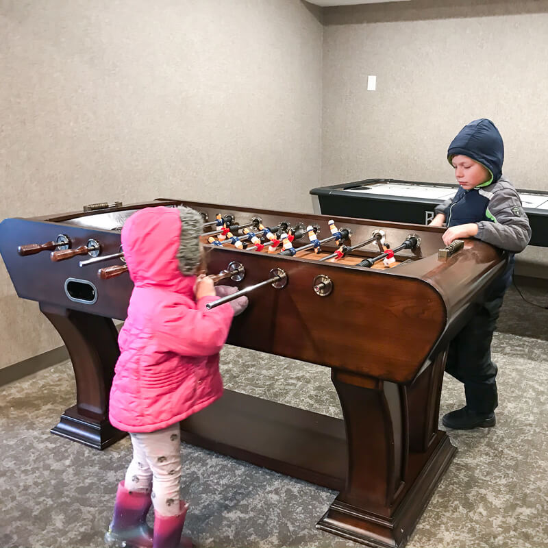 Two small kids playing inside the game room at Hotel Azure.