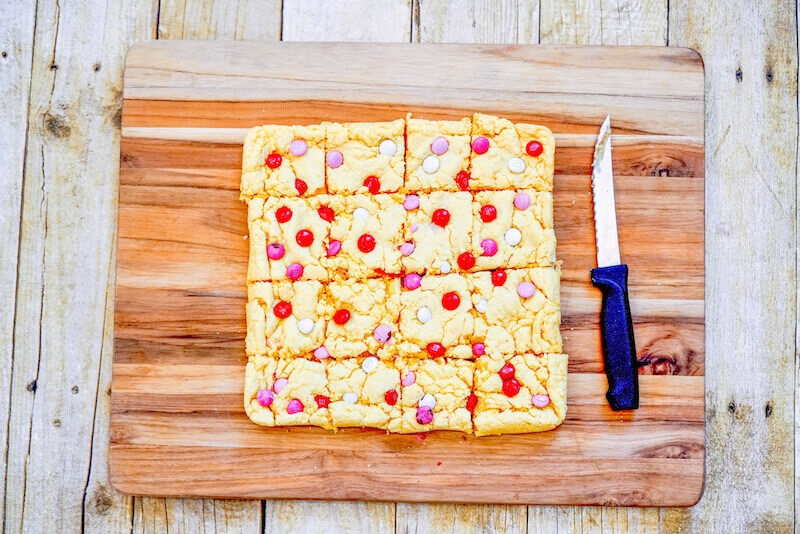A wooden cutting board with cooled cake mix bars cut into 16 squares.