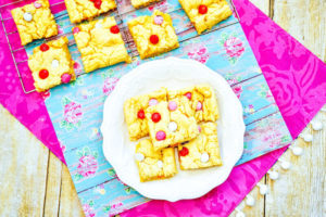 A pink tablecloth topped with a floral placemat with a cooling rack of cookie bars and a white plate of cookie bars on top!