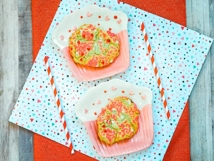 Two cupcake shaped plates with valentine's sprinkle cookies on them.
