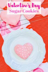 White decorative plate with one pink and white heart shaped cookie.