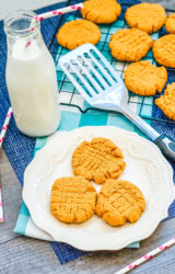 Bottle of milk next to a pretty white plate with three peanut butter cookies.