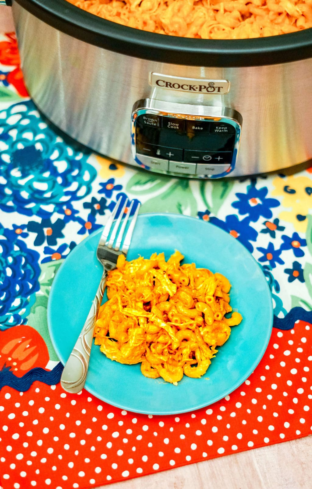 A plate of Mac and cheese on a floral tablecloth.