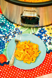 A blue plate with crockpot Mac and cheese.