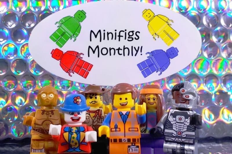 "Several LEGO figurines with a sign that says ""minifigs monthly""."