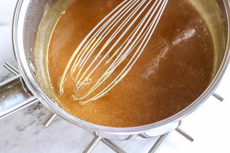 A whisk inside gravy on stove.