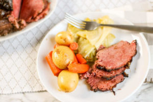 A white plate with gold potatoes, sliced carrots, cabbage, and three slices of corned beef.