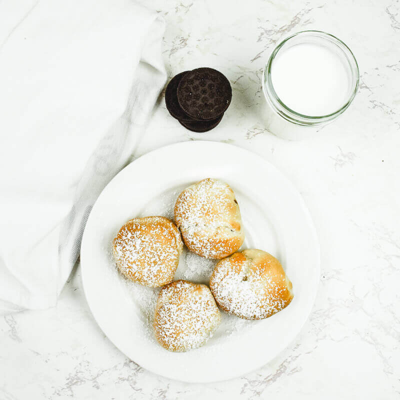 Overhead shot of four air fried Oreos coated in powdered sugar on a white plate.