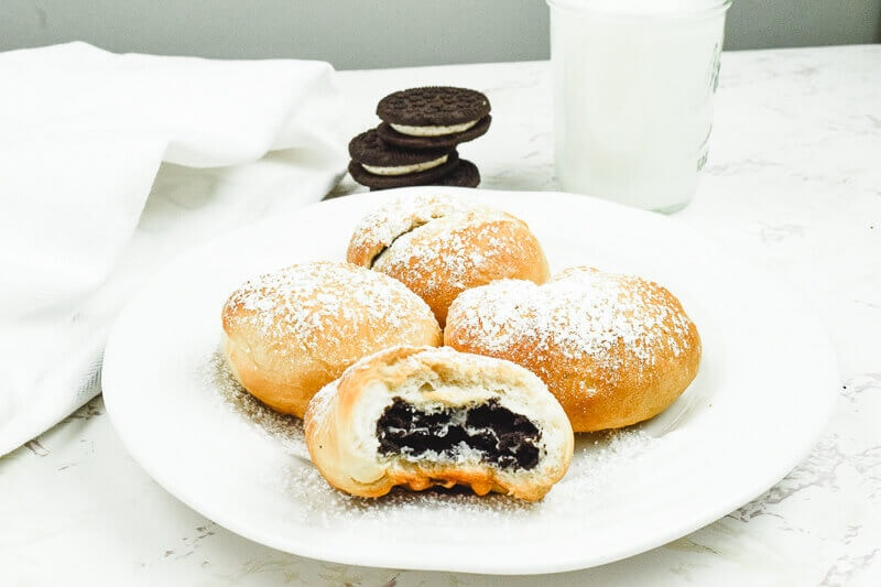 A white plate of air fried Oreos with Oreos stacked up in the background.