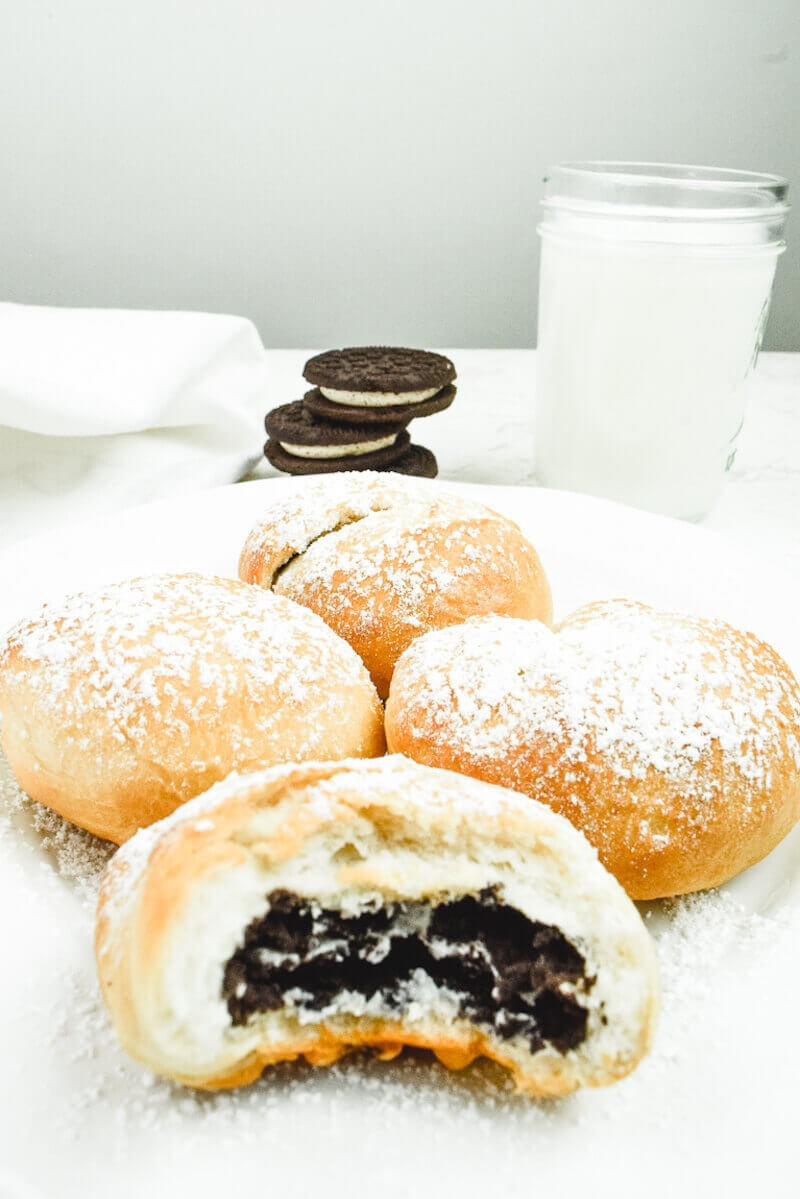 A half-eaten air fryer oreo in front of three more fried Oreos, a glass of milk, and a stack of oreo cookies.