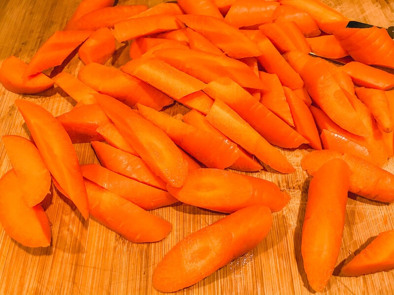 Cut up carrots on a wooden cutting board.