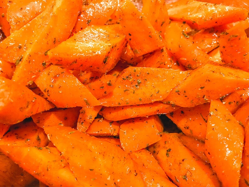 Close up of carrots evenly coated with oil, herbs, and spices.