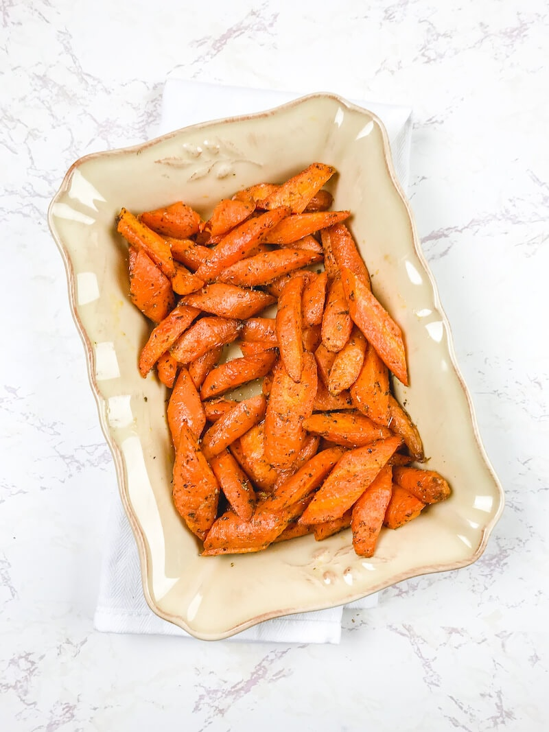 A beige serving dish filled with air fried carrots.