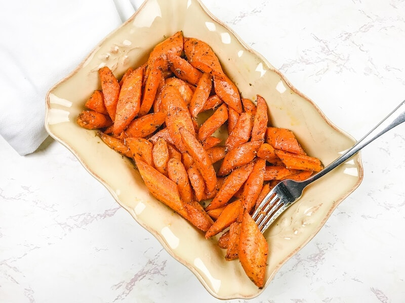 A beige serving dish filled with roasted carrots and one on a fork.