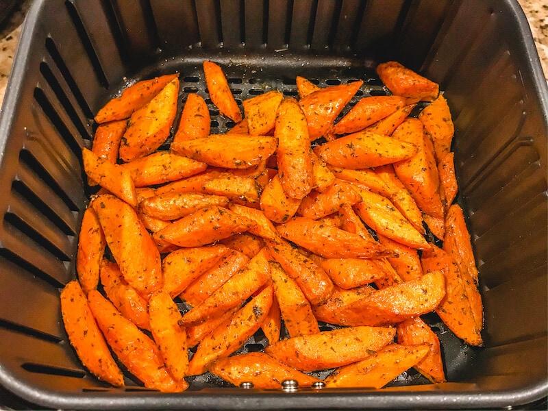 Air fried carrots inside of black air fryer basket.