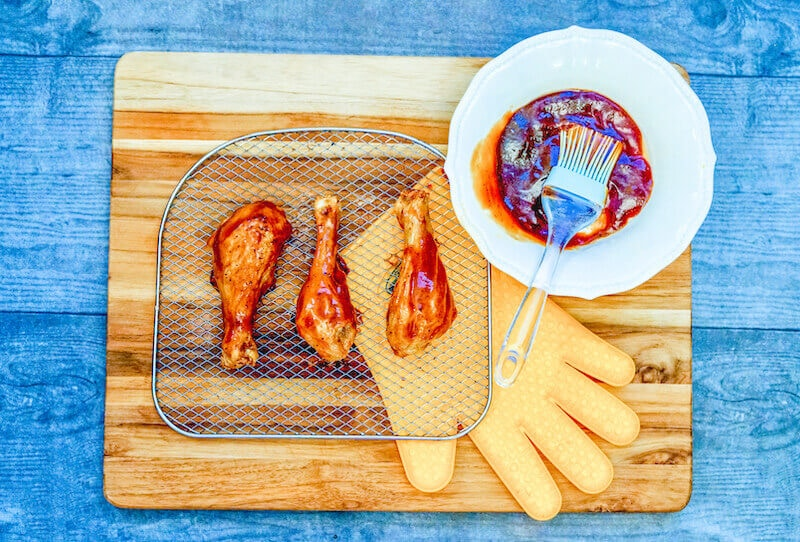 An air fryer tray coated with bbq sauce.