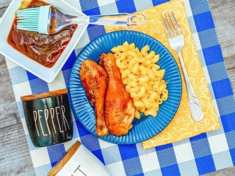 A blue and white checked placemat topped with a blue plate of drumsticks coated with barbecue sauce.