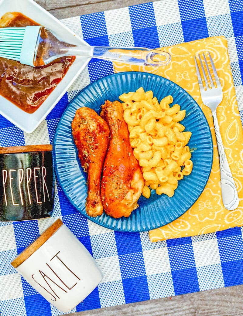 Blue and white checkered placemat topped with a blue plate of bbq air fryer drumsticks.
