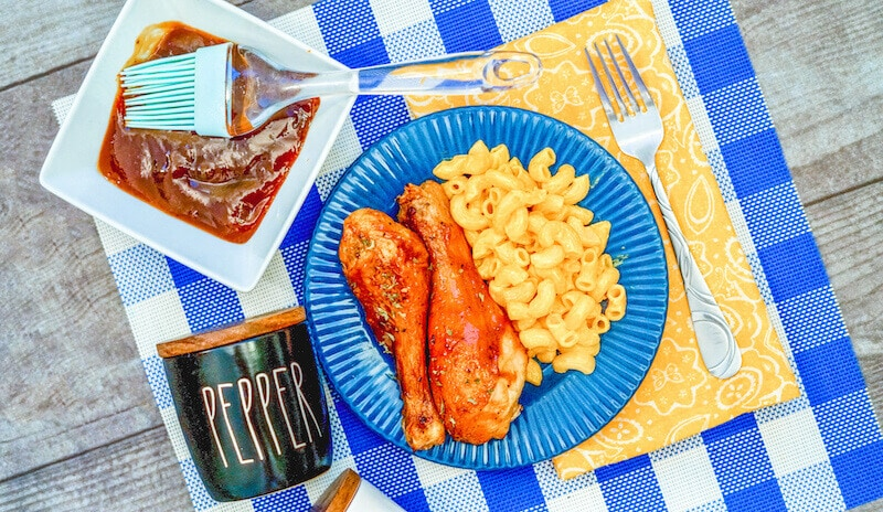 A blue plate filled with air fryer drumsticks and Mac and cheese.