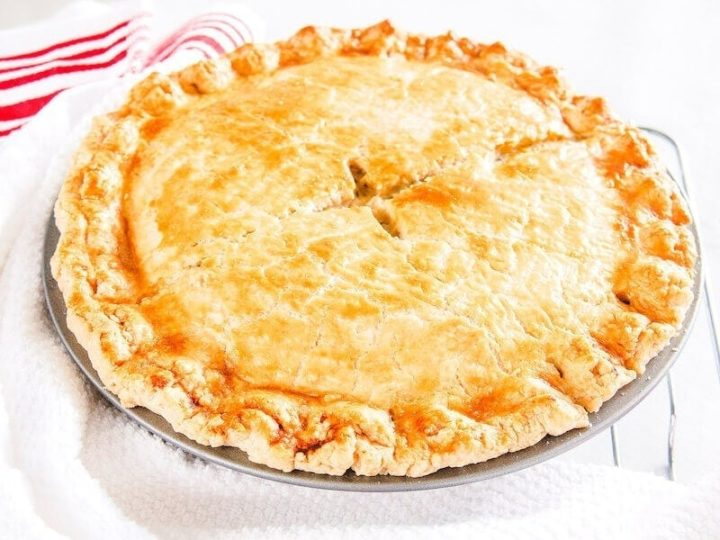 A freshly baked chicken pot pie on a white tablecloth.
