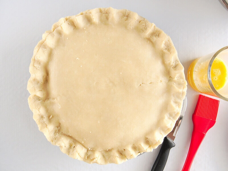 Chicken pot pie prepared with second crust on top and edges of crust crimped.