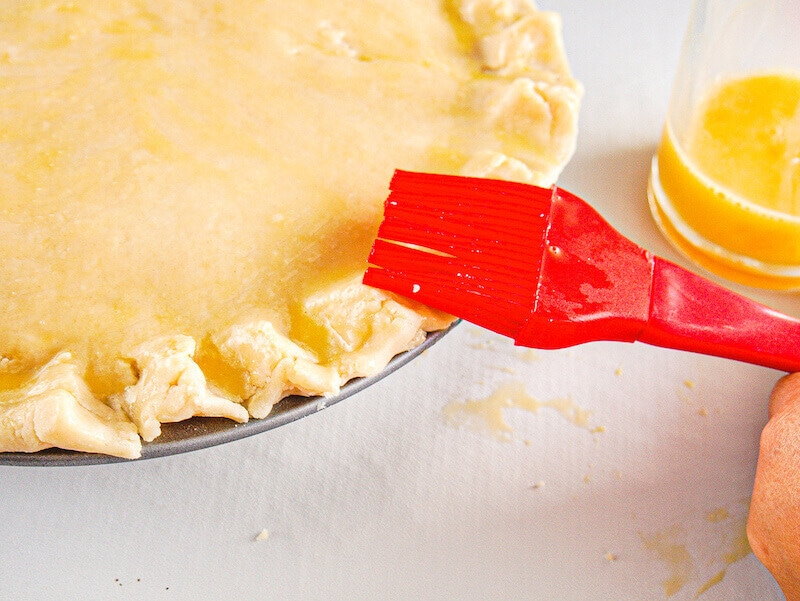 A pastry brush brushing egg wash onto pie crust.