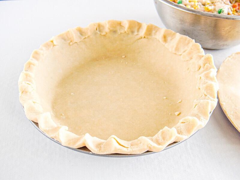 A pie crust inside of a pie dish.