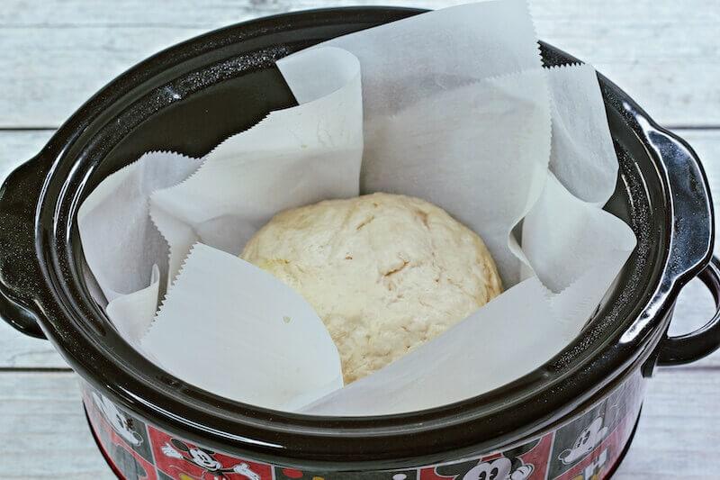 Doubled dough inside parchment lined crock pot