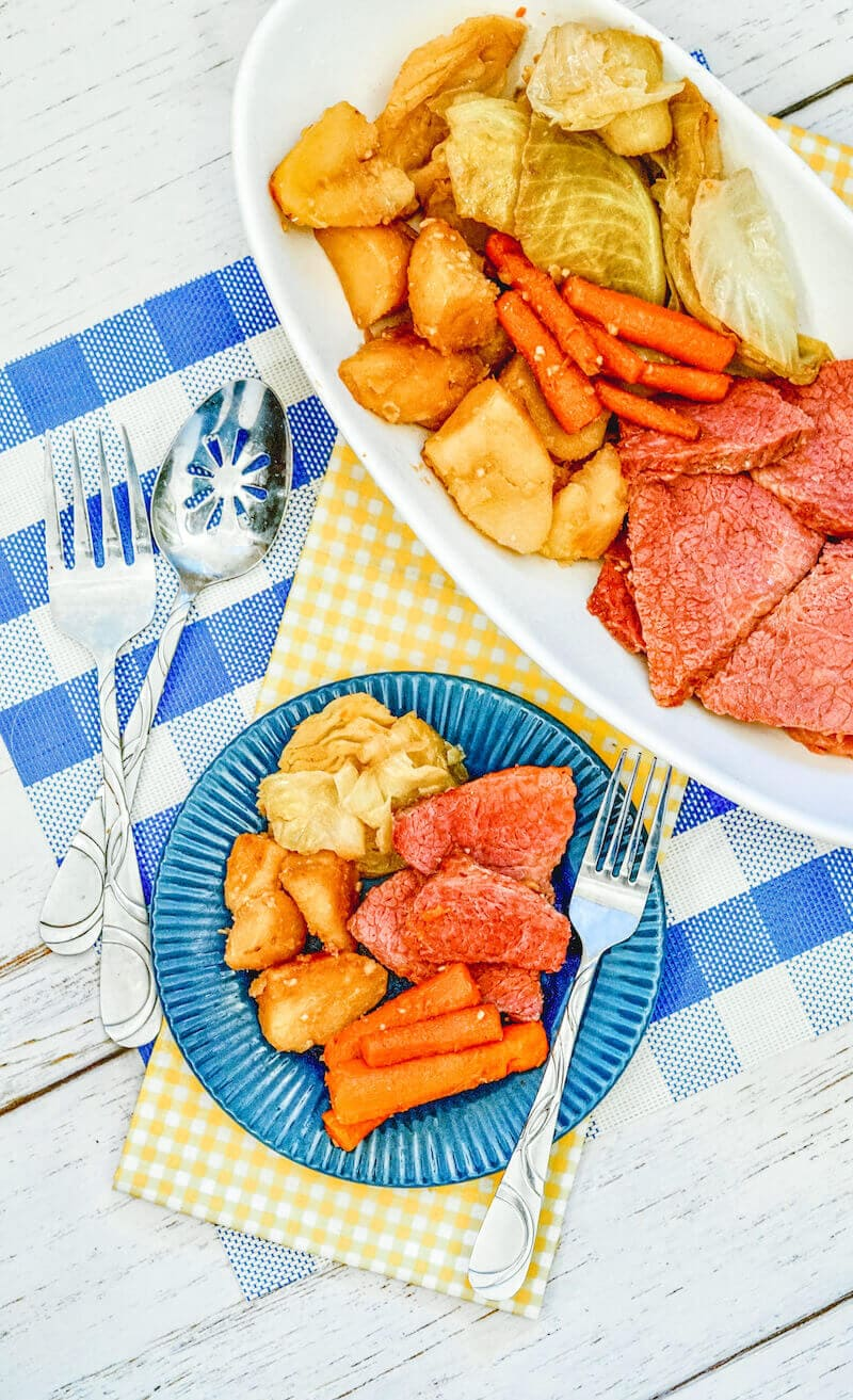 A blue plate of corned beef, potatoes, carrots, and cabbage with a fork next to it.