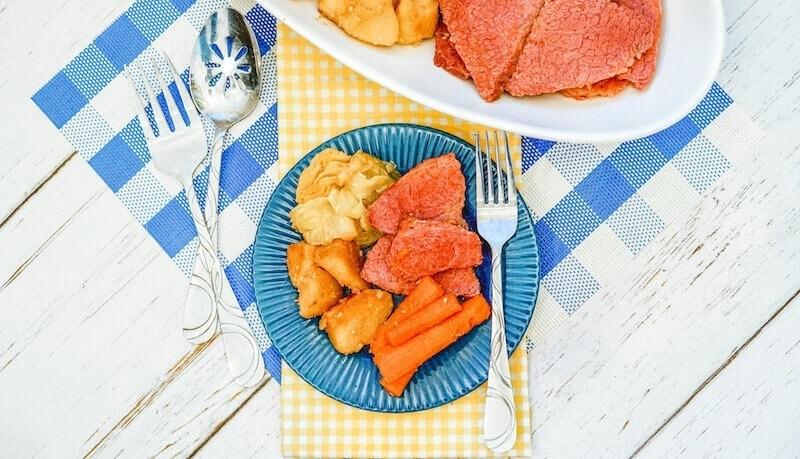 A blue checkered place mat topped with a plate of corned beef with potatoes and carrot.