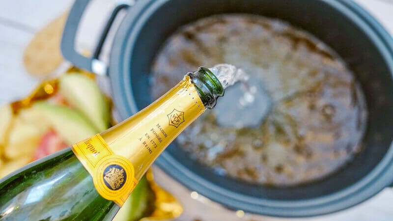 Champagne being poured into crock pot.