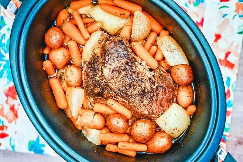 Overhead shot of crockpot roast with gravy inside crockpot.