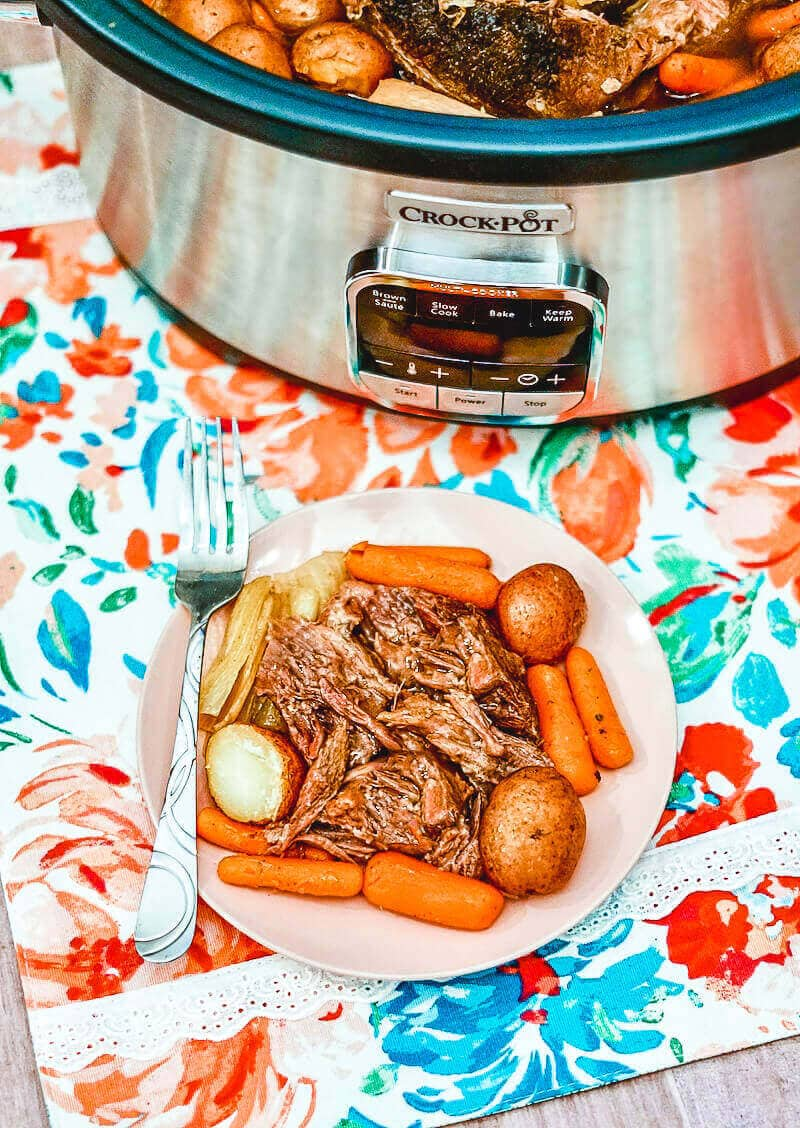 A plate of roast beef in front of a crockpot.