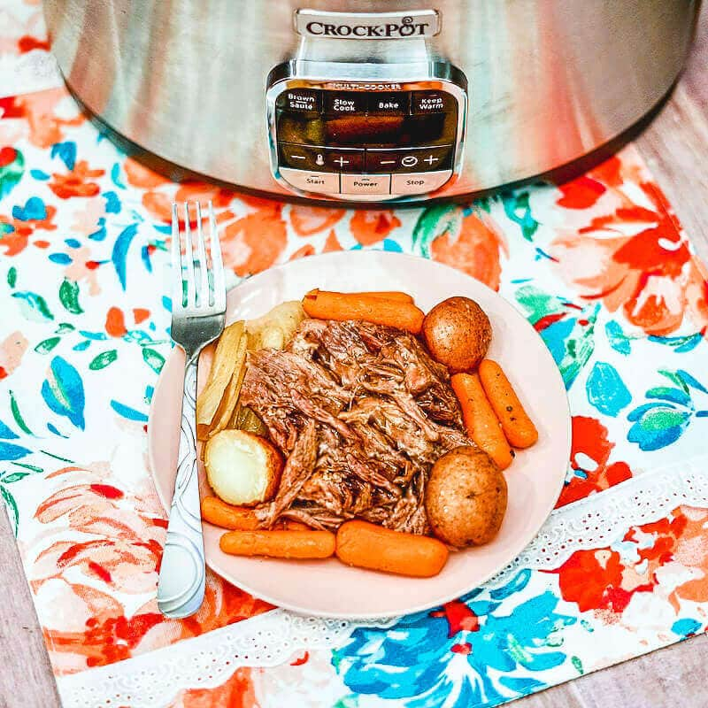 A white plate of pot roast with gravy, potatoes, and carrots.