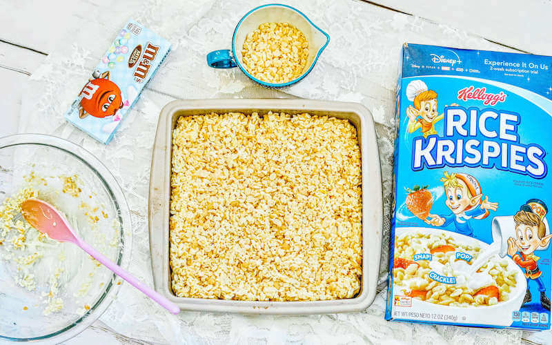 Rice Krispie treats batter pressed into square baking dish.