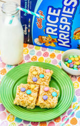 Close up of Rice Krispie treats on a green plate with cereal box in the background.