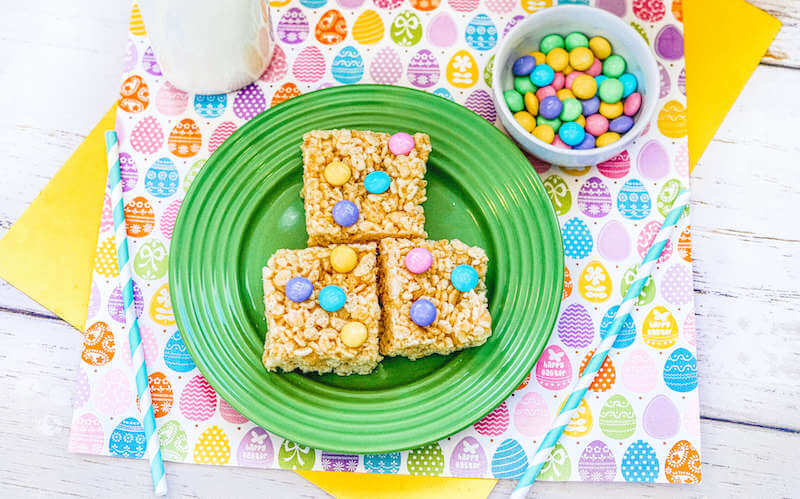 Green plate with three Easter themed Rice Krispie treats next to a bottle of milk.