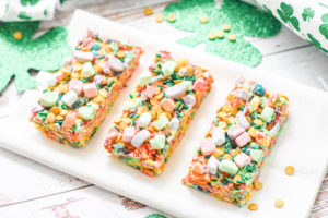 Three fruit pebbles bars on a white platter.