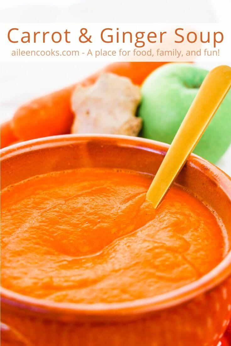 "Close up of carrot soup with words ""carrot & ginger soup"" in orange letters."