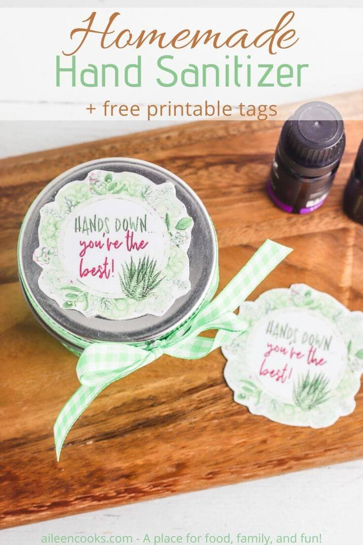 Overhead shot of jar of hand sanitizer with gift tag and green ribbon.