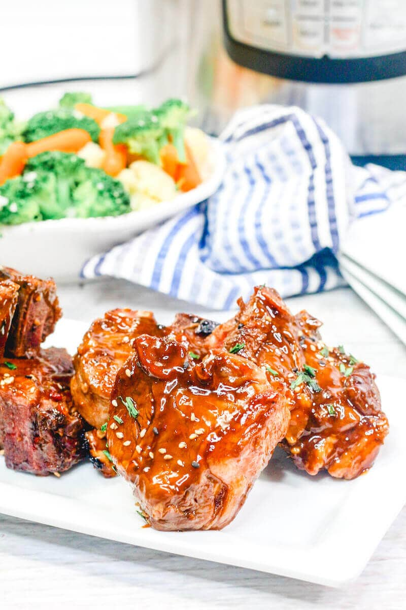 Lamb chops on a platter with blue striped towel in background.