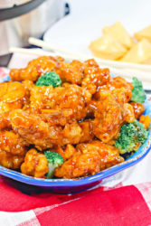 Close up of orange chicken in a blue bowl.